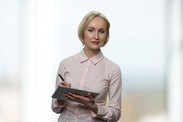성공한 여성이 태블릿에 무언가를 쓰고 있습니다. 배경에 windows와 함께 아름 다운 백인 금발 사업가입니다.