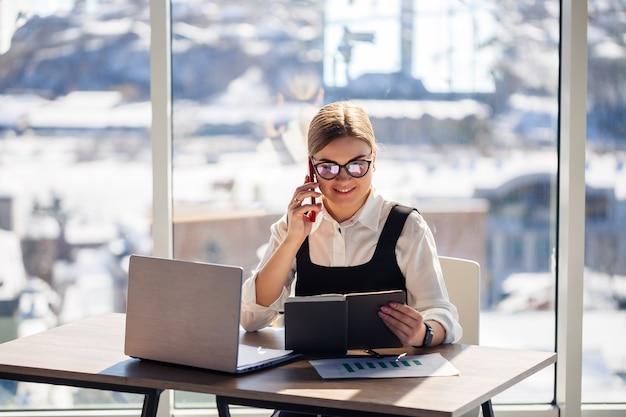 Успешная женщина-наставник, директор, бизнесмен в очках и костюме изучает документы, сидя за столом. концепция рабочего дня