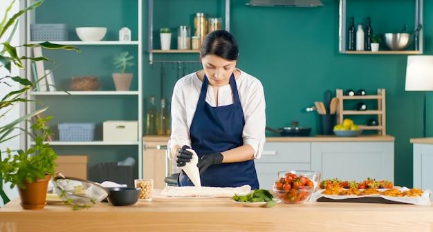 성공적인 여성 페이스트리 셰프는 요리 가방을 사용하여 케이크에 크림을 짜냅니다