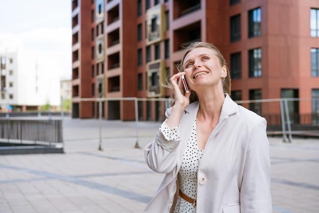 スタイリッシュな笑顔のビジネスのストリートポートレートを歩いて電話で話している成功した女性...