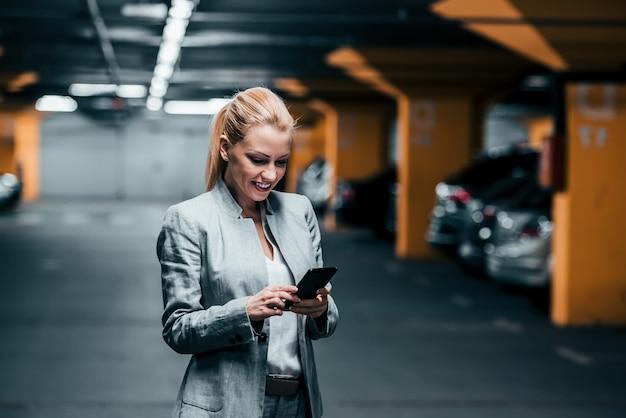 Успешная женщина, с помощью телефона в подземном паркинге.