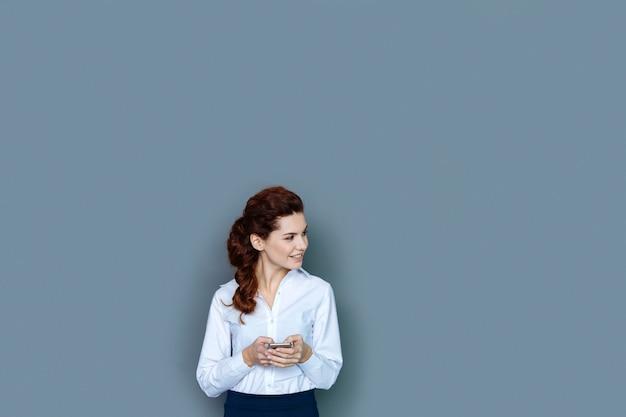 成功した女性。彼女のプロの成功に満足している間、笑顔で脇を見て喜んでポジティブな魅力的な女性