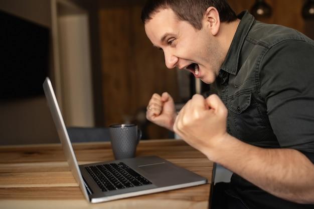Успешная работа из дома. счастливый человек работает на ноутбуке в помещении