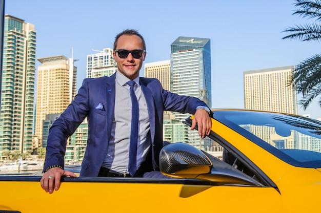 黄色のカブリオレ車で成功したヤンビジネスマン。
