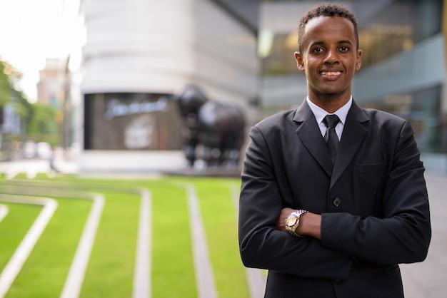腕を組んで屋外で笑って成功した若いアフリカの実業家