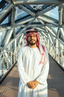 현대 비즈니스 센터 내부의 긴 통로를 배경으로 카메라 앞에 서 있는 국가 복장을 한 성공적인 젊은 아랍 남성 대표