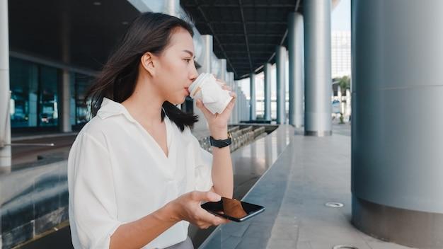 Giovane imprenditrice asiatica di successo in abiti da ufficio alla moda che tiene in mano una tazza di carta usa e getta di bevanda calda e usa lo smartphone mentre si sta in piedi all'aperto nella città moderna urbana
