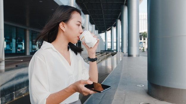 都会の近代的な都市で屋外に立っている間、ホットドリンクの使い捨て紙コップを保持し、スマートフォンを使用してファッションオフィス服で成功した若いアジアの実業家