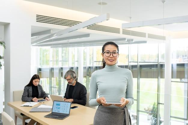 Успешная молодая азиатская бизнес-леди в очках и повседневной одежде стоит перед камерой против двух коллег, использующих гаджеты