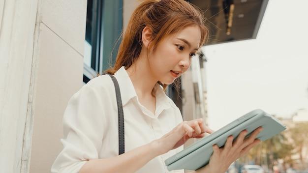 디지털 태블릿을 사용하고 텍스트 메시지를 입력하는 패션 사무실 옷에서 성공적인 젊은 아시아 사업가