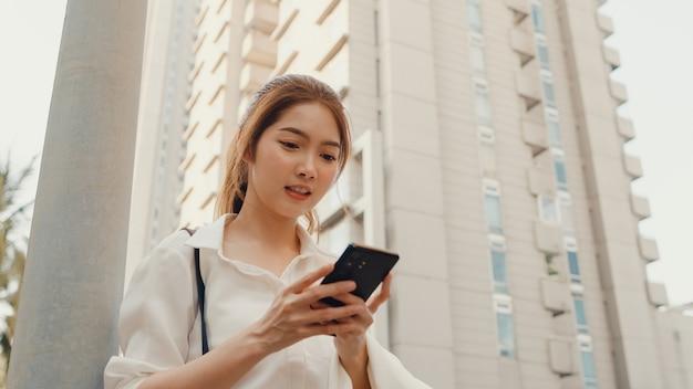 スマートフォンを使用してテキストメッセージを入力してファッションオフィス服で成功した若いアジアの実業家
