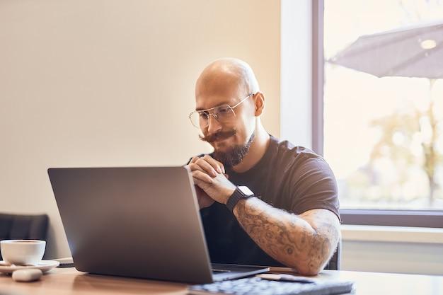 Успешный молодой лысый человек, глядя на ноутбук, работая в концепции внештатного домашнего офиса