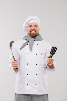 孤立して笑顔であなたを見ながら台所用品を保持している制服を着た成功した若いひげを生やしたシェフ