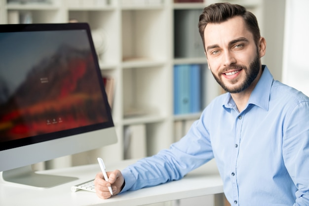 Successful young bearded designer or analyst looking at you while planning work by desk in office