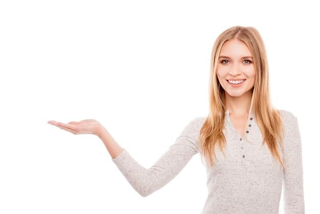 新製品を提示する成功した若いブロンドの女性