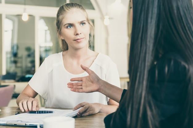 Успешные молодые бизнес-леди встречаются в коворкинге для подписания соглашения