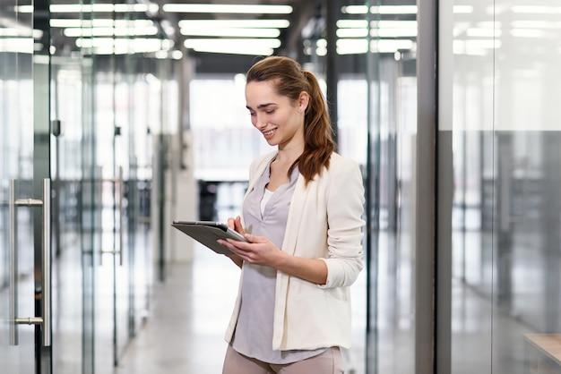 사무실 복도 따라가는 동안 태블릿 pc에 안경 개정 회사 정보에서 성공적인 젊은 비즈니스 아가씨.