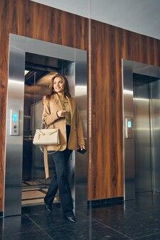 Успешная молодая бизнес-леди с модной сумкой выходит из лифта офиса и улыбается