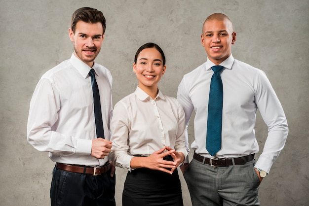 Successful young business partners looking to camera standing against grey wall