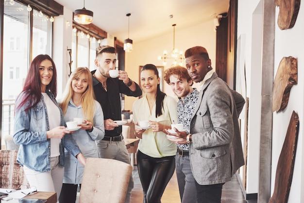 成功した若いビジネス人は話して、オフィスでのコーヒーブレーク中に笑顔