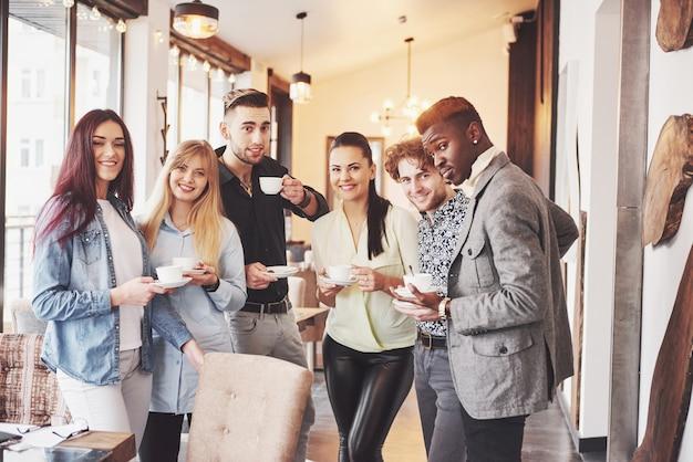 成功した若いビジネス人々は話して、オフィスでのコーヒーブレーク中に笑顔