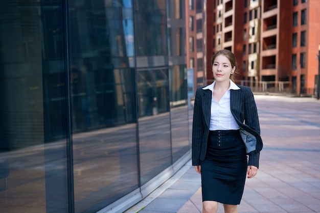 Successful young business woman on the background of an office building in a black suit