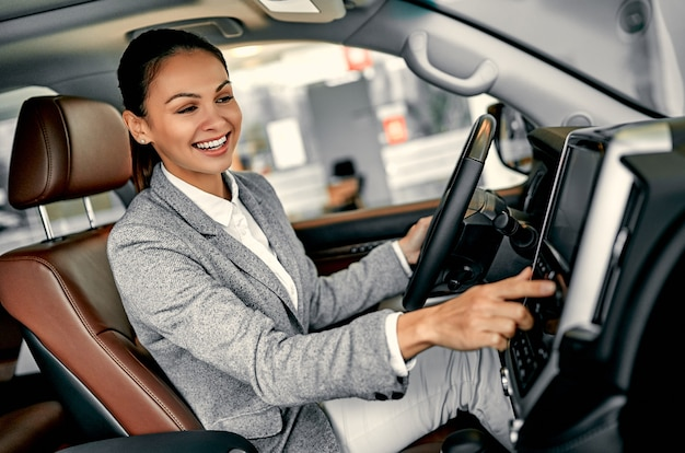 Successful young business woman using navigation system while driving a car.
