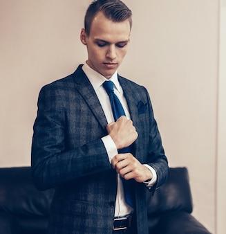 Успешный молодой бизнесмен поправляя запонки.