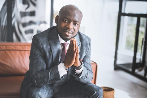 スタイリッシュで高価なスーツを着た成功した青年実業家アフリカ系アメリカ人の男は、手のひらを一緒に折りました...