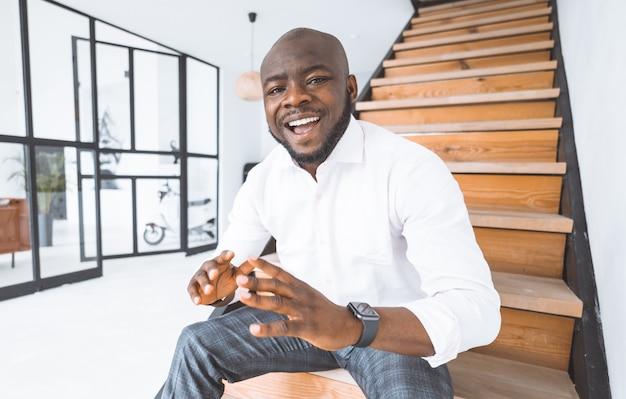 成功した青年実業家アフリカ系アメリカ人の男は彼のサクセスストーリーを共有します若い男は階段に座っています...