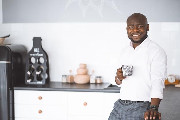 成功した青年実業家アフリカ系アメリカ人の男が手にカップを持ってキッチンで笑っている豊富な投資家...