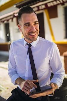 Giovane imprenditore di successo in un abito formale utilizzando un tablet
