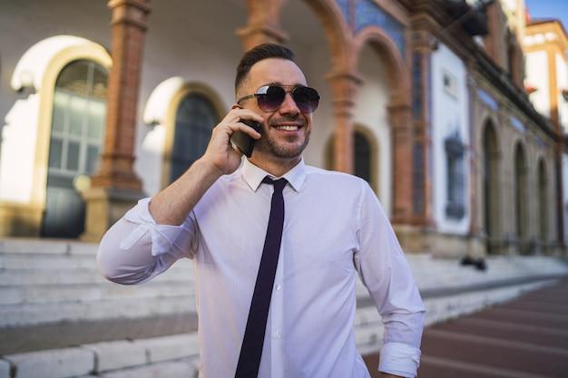 Успешный молодой бизнесмен в официальном наряде с солнцезащитными очками разговаривает по телефону