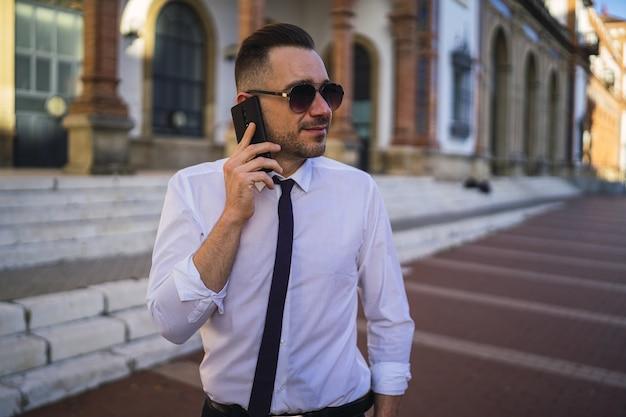 전화 통화하는 선글라스와 공식적인 복장에서 성공적인 젊은 사업가