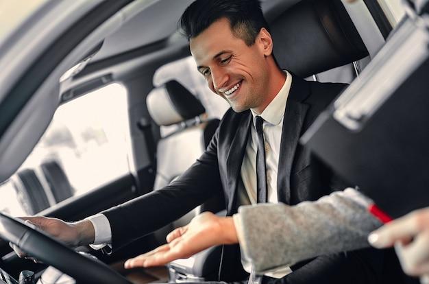 양복을 입은 성공적인 젊은 사업가가 새 차를 선택합니다. 판매자가 차 선택을 돕습니다.