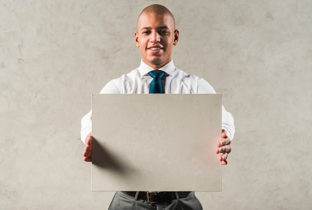 Successful young businessman showing grey placard standing against wall
