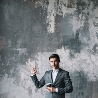 Successful young businessman standing against concrete wall holding cup of coffee pointing his finger upward