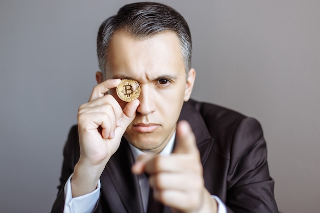 Successful young businessman in suit with bitcoin on gray
