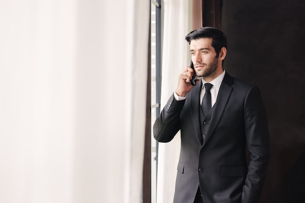 Successful young businessman talking on cellphone near windows