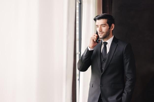 窓の近くで携帯電話で話す成功した青年実業家