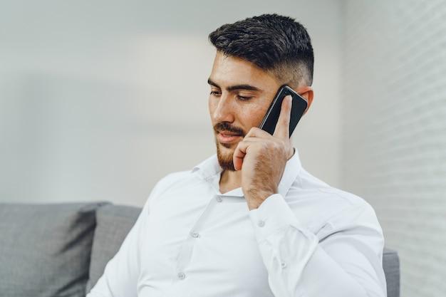 彼の携帯電話で話している成功した青年実業家