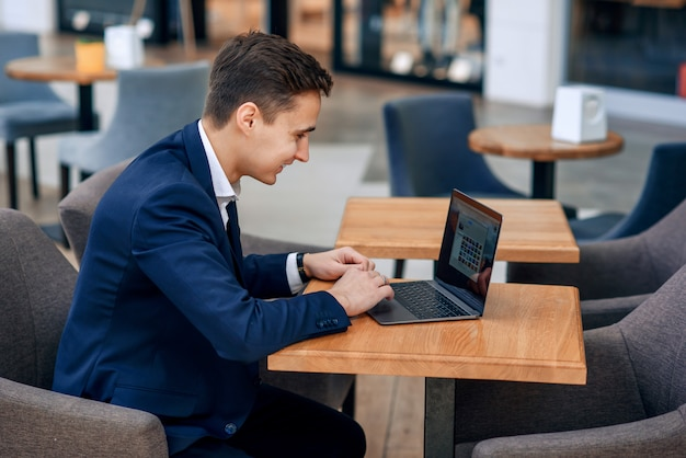 Successful young businessman working on laptop in coffee shop
