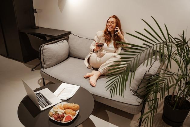 生産的な営業日とお得な情報の後にスマートフォンで通信する成功した若い実業家。彼女はグラスワインを持っており、テーブルには果物とクロワッサンがあります。