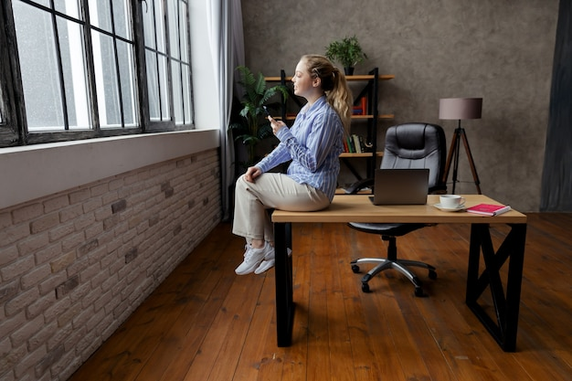 Successful young businesswoman hold phone, sitting on desk and looking at window. high quality photo