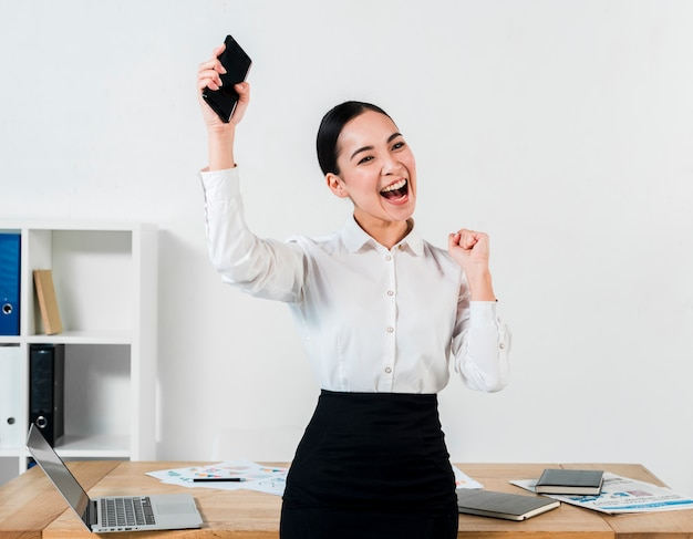 Successful young businesswoman holding mobile in hand clenching her fist at workplace