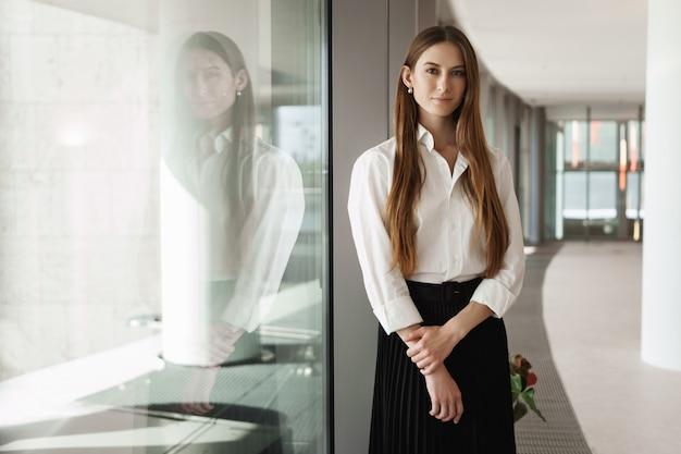 Успешный молодой предприниматель, стоя у окна в коридоре офиса, улыбаясь и глядя в камеру.