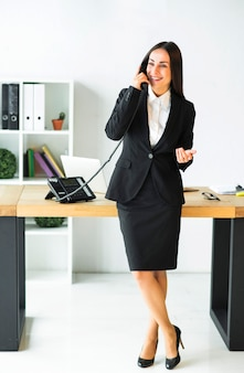 Successful young businesswoman standing with crossed leg in front of desk talking on telephone