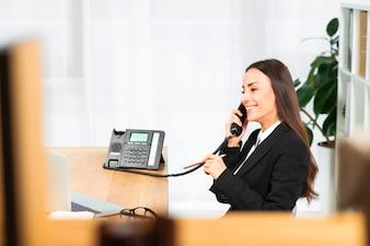 手に鉛筆で電話で話している成功した若い実業家