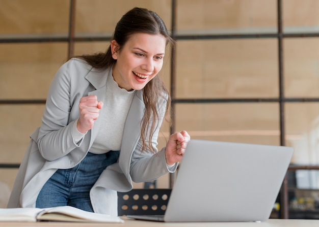 Successful young businesswoman with clenched fists looking at laptop