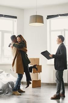 成功した若いカップルが住宅所有者になりました。女の子が彼のボーイ フレンドの腕に飛び込む。大きな窓のある明るく広々とした家。